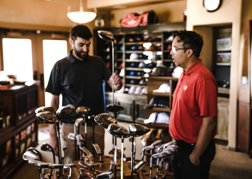 Man Standing Beside Man Holding Gray Golf Club