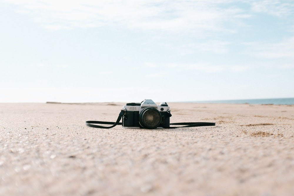 black and silver SLR camera on seashore